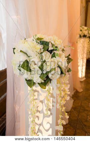Wedding floristry. Arrangement of peonies on the high luminous rack.
