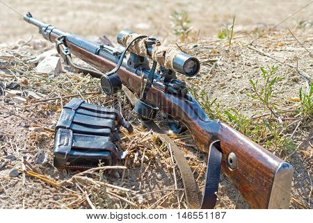 old rifle with telescopic sight on position