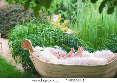 Wooden cradle in the form of the boat on a green grass. The baby lies having raised legs on a white fluffy blanket