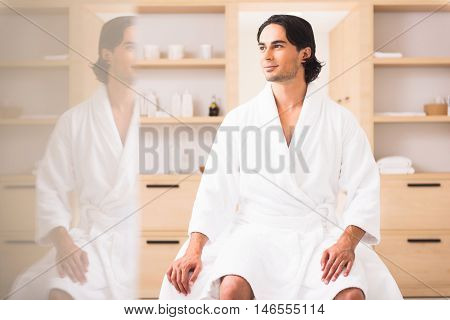 Relaxed young man is resting at spa. He is sitting in bathrobe and dreaming