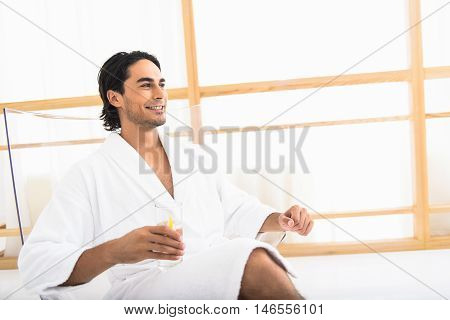 Cheerful young guy is enjoying fresh drink on vacation. He is sitting in restroom and holding glass. Guy is smiling