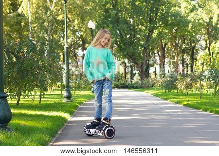 A Little Girl Riding A Electric Scooter .she Folded Her Hands In Pocket And Looks Away . Personal Ec
