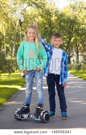 Girl Standing On Mini Segways . Boy Does It Horns . They're Laughing Together And Smiling .