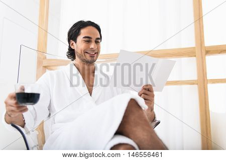 Relaxed young man is enjoying his vacation. He is sitting on chair and reading book. Man is holding cup of coffee and smiling