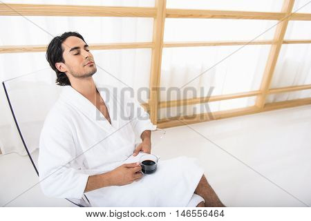 Young man is relaxing in morning. He is sitting on chair in bathrobe and holding cup of coffee. His eyes are closed with pleasure