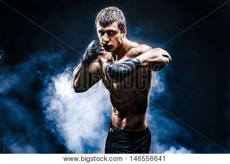 Muscular kick-box or muay thai fighter punching in smoke.