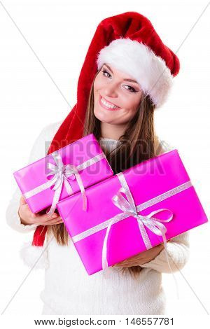 Christmas winter happiness concept. Woman wearing santa helper hat holding stack of pink presents gift boxes isolated on white