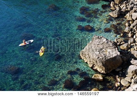 Two tourists on a kayak pass by a steep rocky shore of the sea in the Crimea. Beautiful sports holidays