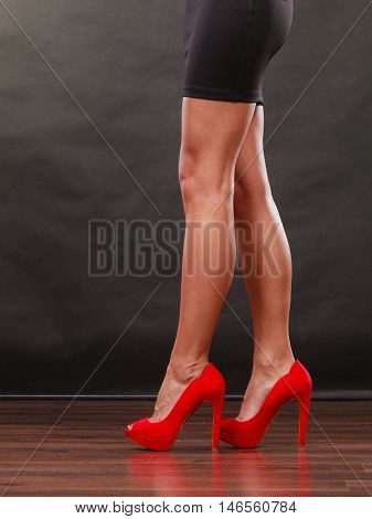 Female fashion. Closeup red high heels spiked fashionable shoes on sexy female legs