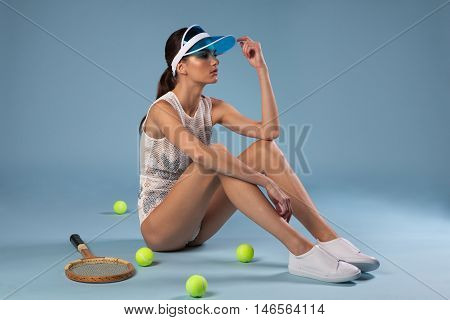 stylish brunette woman sitting on floor near tennis racquet and balls on blue background