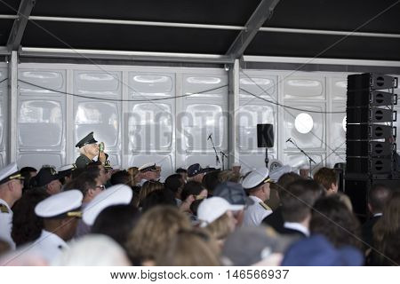 NEW YORK MAY 30 2016: A US veteran stands to take a picture of the speakers during the Memorial Day Observance service on the Intrepid Sea, Air & Space Museum during Fleet Week NY 2016.