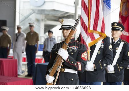NEW YORK MAY 30 2016: Military personnel from the U.S. Armed Forces Honor Guard present colors during the Memorial Day Observance service on the Intrepid Sea, Air & Space Museum, Fleet Week NY 2016.