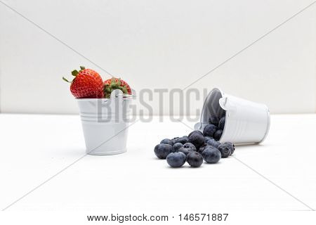 A full bucket of strawberries and an empty bucket of blueberries