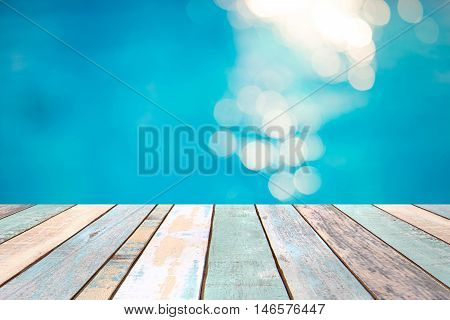 Perspective wood table top and Soft focus bokeh light effects over a rippled blue water background in the pool product display montage