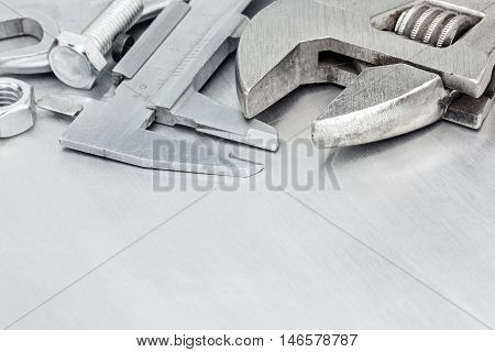 Wrenches, Caliper, Screws On Scratched Metal Surface Background For Hand Work And Renovation