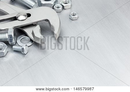 Pliers, Screws And Bolts Of Different Size For Work On Scratched Metal Background