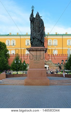 MOSCOW RUSSIA - JULY 23 2016: Unidentified people relax in Alexandrovsky Garden of Moscow Kremlin near monument to Hieromartyr Hermogenes Patriarch of Moscow and All Russia