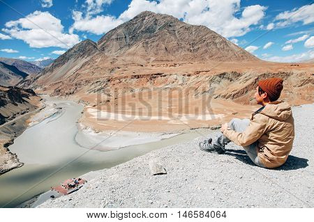 Young happy man sitting on the cliff on the trip in Indus River in Leh, Ladakh, India