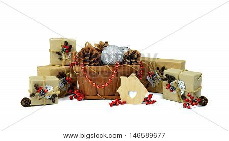 . Preparations for Christmas in the countryside. The composition in a rustic style with gifts berries pine cones toys and beads. / Isolation on a white background /.A pile of Christmas gifts handmade. Christmas-tree tinsel.