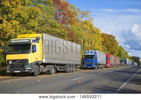 LENINGRAD REGION, RUSSIA - SEPTEMBER 27, 2015: The queue of trucks on the highway M-11