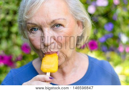 Elderly Woman Enjoying A Refreshing Iced Lolly