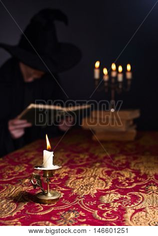 Candle on the background of the reading wizard focus on foreground
