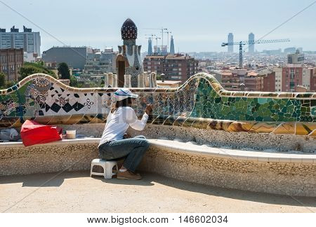 JUNE 16 2011 - BARCELONA SPAIN: Professional restorer working at colorful ceramic bench in Parc Guell. Barcelona. Spain