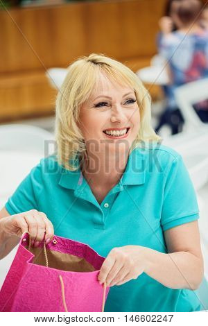 Happy mature woman is receiving gift with surprise. She is opening packet and smiling. Woman is sitting in cafe