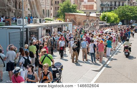 JUNE 16 2011 - BARCELONA SPAIN: Tourists queue to buy tickets to visit The Sagrada Familia Cathedral in Barcelona