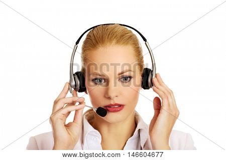 Young woman helpline operator is trying to hear something through headphones