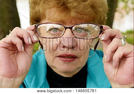 Woman holding glasses before the eyes.She has poor eyesight.
