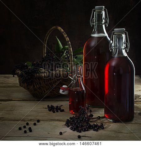 bottles with the red juice from black elderberries (Sambucus nigra) and a basket with berries on rustic wood dark background copy space selected focus