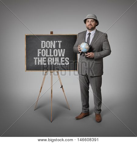 Dont follow the rules text on blackboard with businessman holding globe in hands