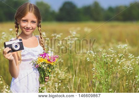 I like photographing nature. Happy girl is holding camera and taking shots. She is standing on meadow and holding flowers. Kid is smiling