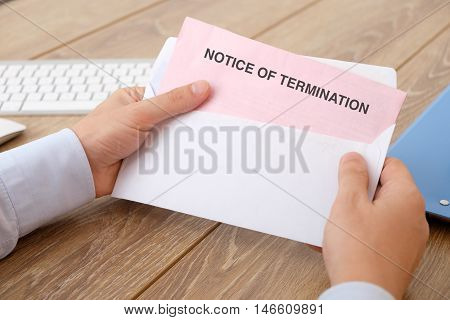 Fired business man reads the notice of job termination