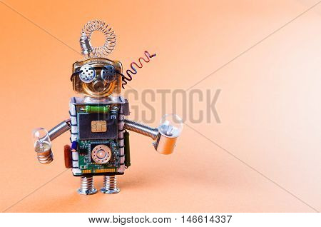 Robot concept retro style. Circuits socket chip toy mechanism, funny head, eyes glasses, light bulbs in hands. Copy space, orange background