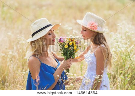 Carefree mother and daughter are enjoying smell of meadow flowers. Their eyes are closed with pleasure. Girl is standing and smiling
