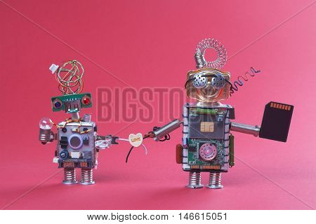 Two robots in love holding hands wire and plastic love heart. Pair retro style robotic mechanism characters black microchip lamp bulbs.