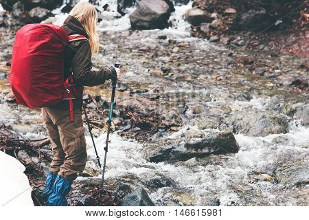 Traveler Woman with backpack hiking Travel Lifestyle concept active vacations outdoor river on background rainy moody weather