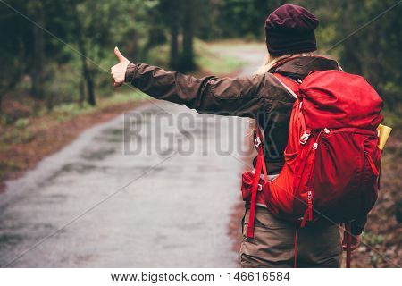 Hitchhiker with red backpack alone on the road Travel Lifestyle concept rear view