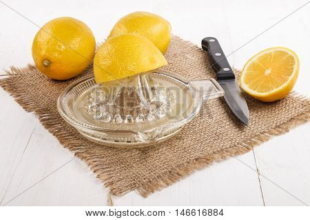 old glass lemon squeezer with fresh juice and kitchen knife on brown jute