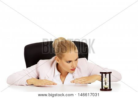 Business woman sitting behind the desk and looking for sandglass