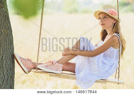 Dreamful girl is relaxing on swing in meadow. She is looking forward and gently smiling