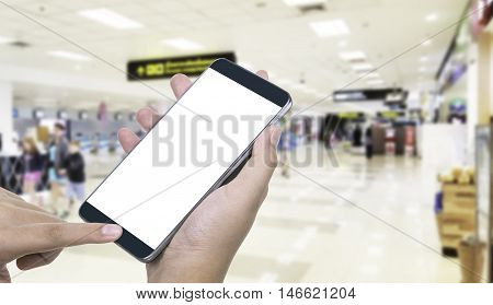 Human hand hold and touch screen smart phone tabletcellphone on blurred in airport background; With clipping path on screen Smart Phone. blank screen for your advertising.