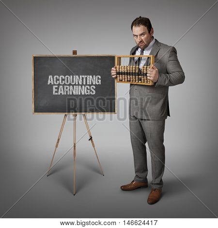 Accounting earnings text on blackboard with businessman and abacus
