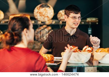 Young baker selling bread to confused woman
