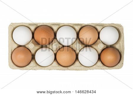 Tolerance concept. Brown eggs among white eggs in box isolated on white background. Top view.