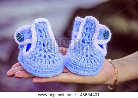 blue booties for newborn baby on the palms