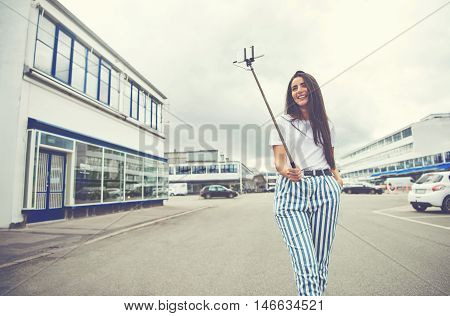 Wide angle view of beautiful woman with hand in pocket taking her own picture in the middle of street under cloudy sky with copy space