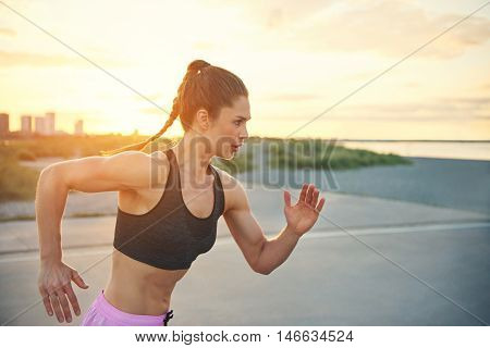 Young female sprinter doing time trials sprinting across the front of the camera with a determined focused expression as she does her daily workout